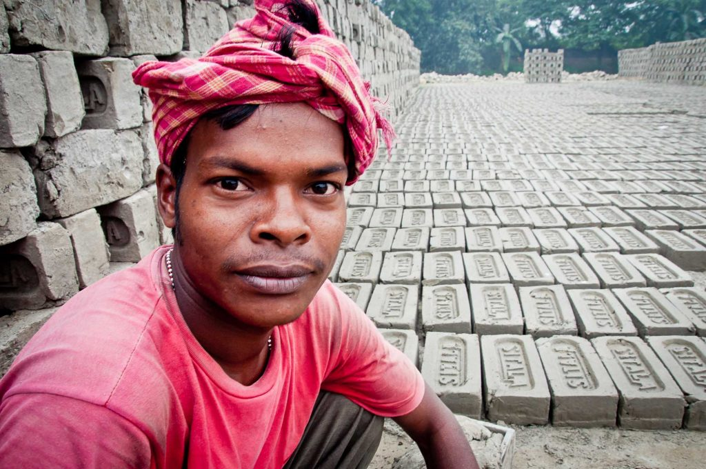 A worker poses as he molds the bricks and leave them for drying under the sun