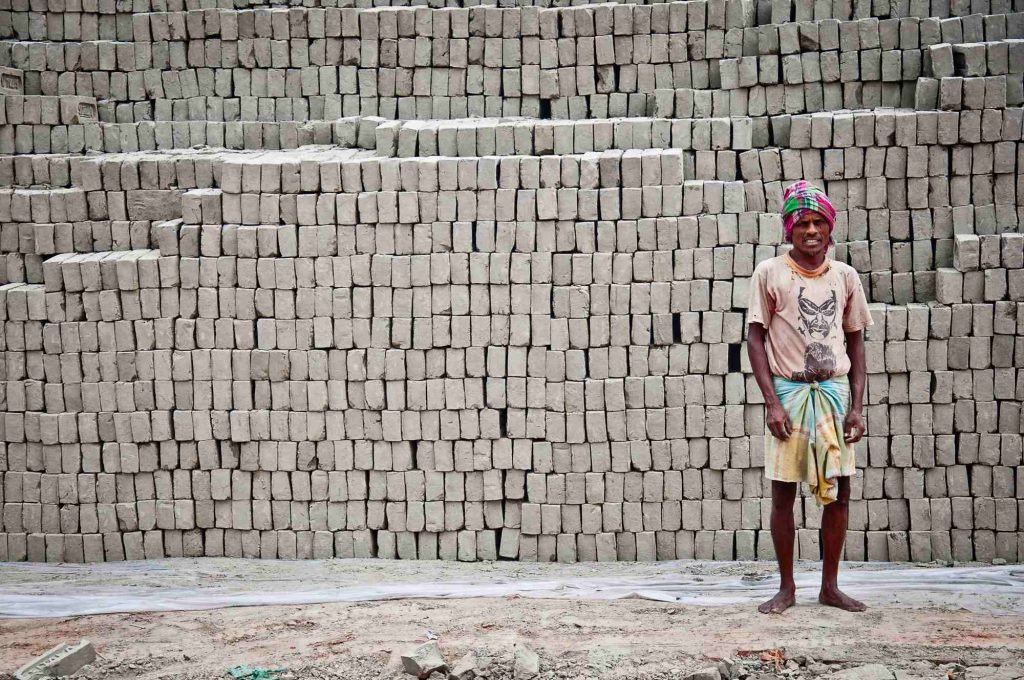 A worker poses in front of a pile of bricks