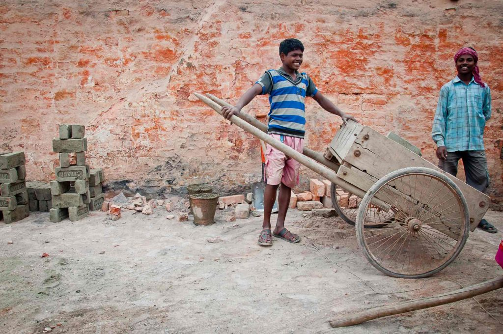 A young worker preparing his cart for carrying the bricks