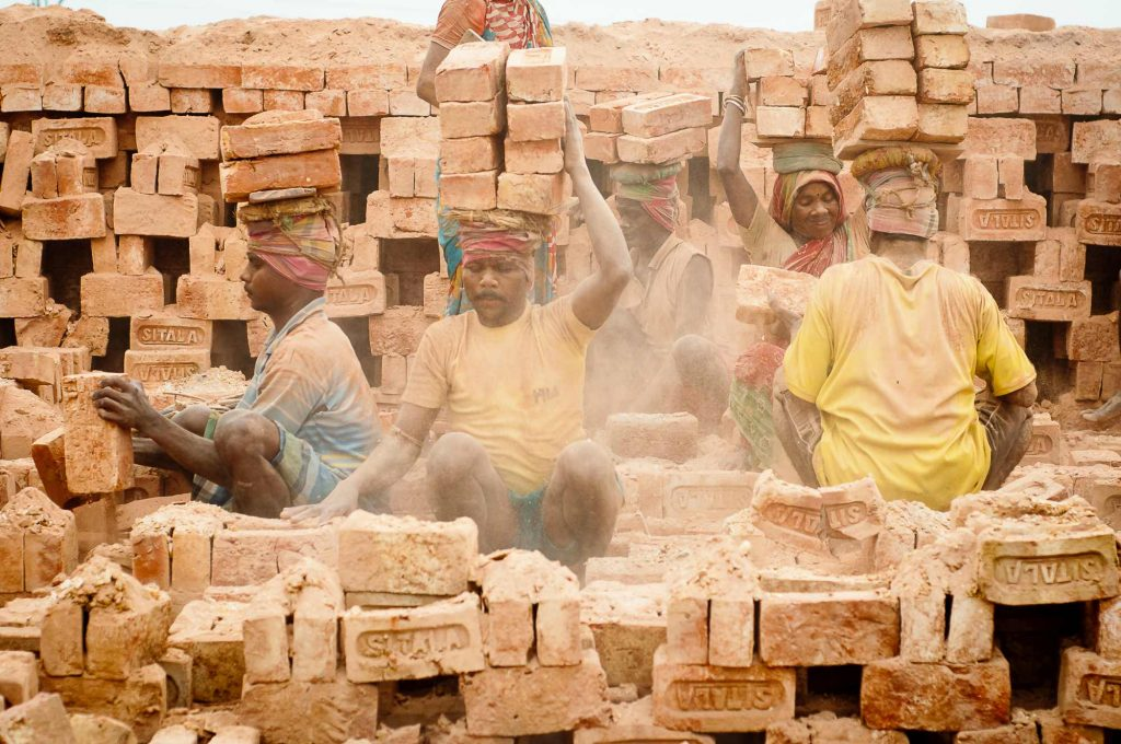 Workers load the bricks on their head and carry to the storage area
