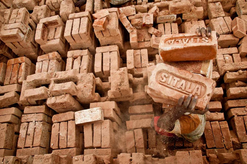 A person loading bricks on top of his head