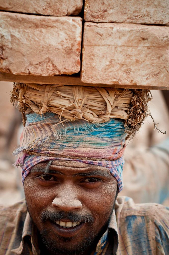 Dust-covered face of a worker carrying bricks