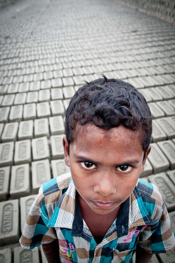 A kid poses as the bricks are left for drying in the sun