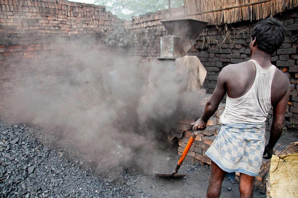 A worker grinding coals to be fed to the furnace
