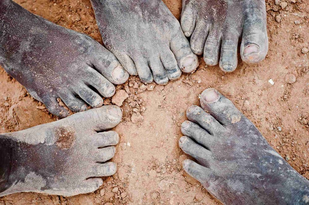 Mud-covered feet of the workers